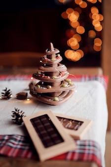 Árbol de navidad hecho de chocolate natural se alza sobre la mesa festiva contra el fondo de luces, ambiente hogareño acogedor