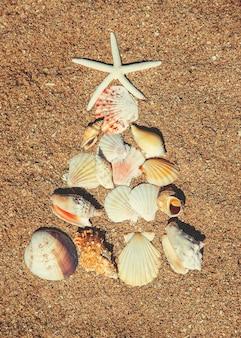Árbol de navidad hecho de conchas en la arena