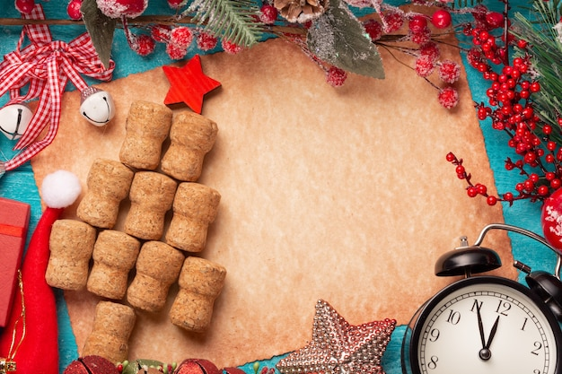 Árbol de navidad hecho con corchos de vino o champán sobre papel antiguo, reloj vintage y adornos.