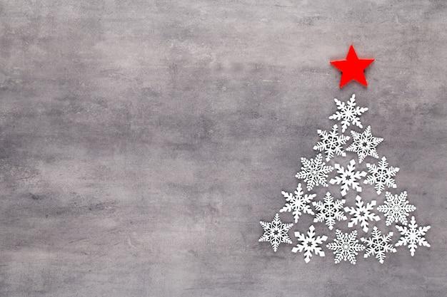 Árbol de navidad hecho de decoración de copos de nieve blanca sobre fondo gris. endecha plana, vista superior