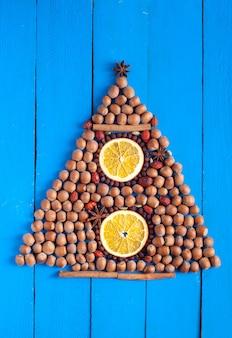 Árbol de navidad hecho de especias, nueces y frutos secos sobre fondo de madera