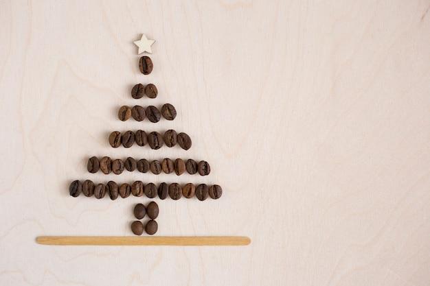 Árbol de navidad hecho de granos de café sobre fondo de madera