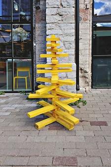 Árbol de navidad hecho de paletas de madera y pintura amarilla.