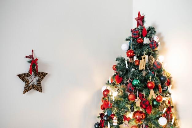 Árbol de navidad con juguetes rojos y verdes sobre un fondo de pared claro