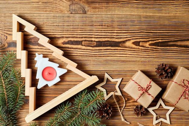 Árbol de navidad de madera con cajas de regalo ramas de abeto conos de pino estrellas de madera sobre fondo de madera