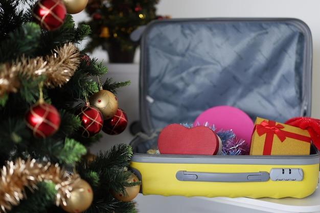 Árbol de navidad y maleta con cajas de regalo viajando en concepto de vacaciones de año nuevo