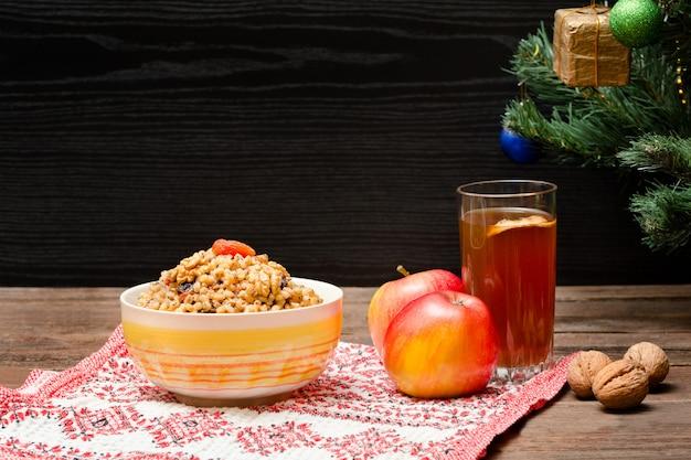 Árbol de navidad, manzanas, nueces, vaso de compota