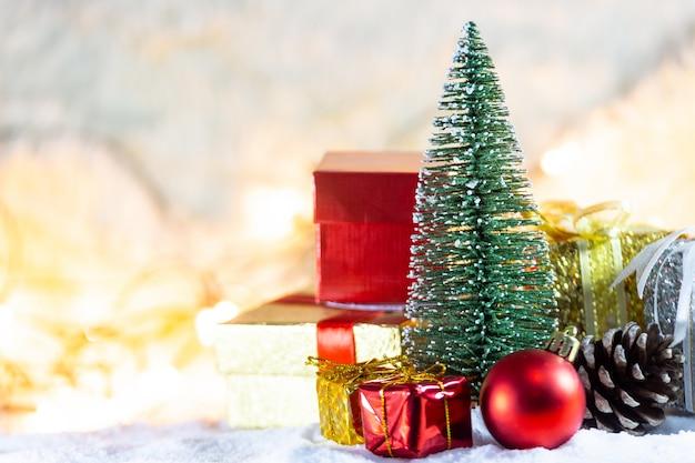 Árbol de navidad en la nieve con fondos de regalo y luz bokeh