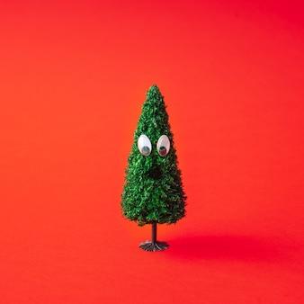 Árbol de navidad con ojos saltones en rojo. concepto de diversión mínima de año nuevo.