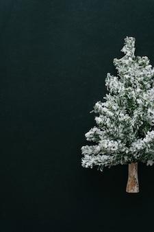 Árbol de navidad en la parte superior de la mesa oscura.