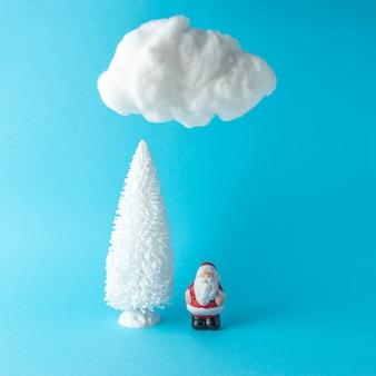 Árbol de navidad con pequeño papá noel bajo una nube de algodón