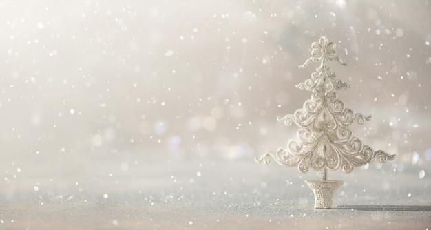 Árbol de navidad de plata del brillo en el fondo gris con el bokeh de las luces, espacio de la copia.
