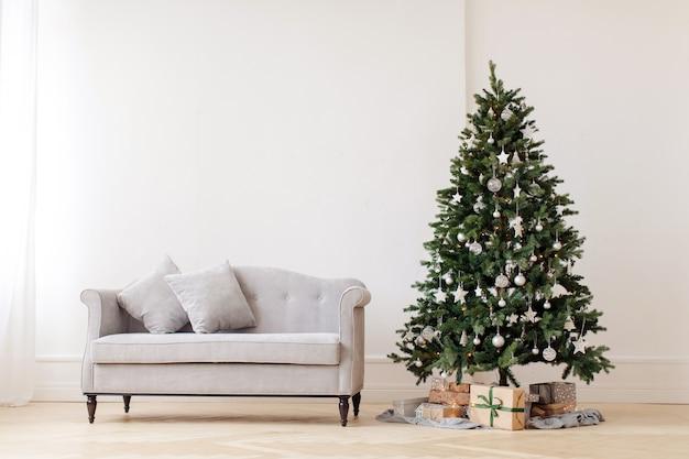 Árbol de navidad y sofá gris.