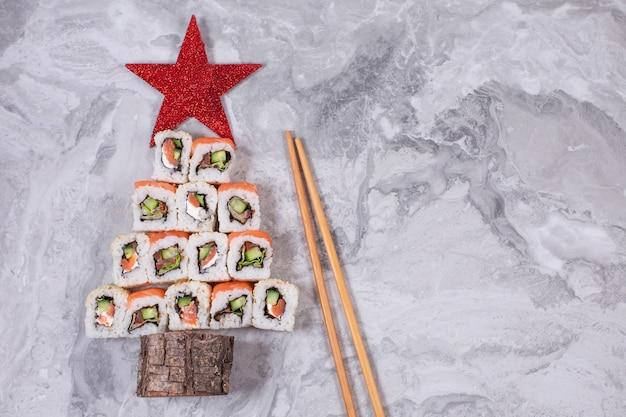 Árbol de navidad de sushi con estrella sobre fondo de piedra