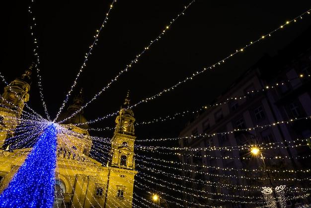 Árbol de pieles de vacaciones con luces en la plaza del mercado de navidad frente a la basílica de san istvan, budapest, noche, diciembre de 2015