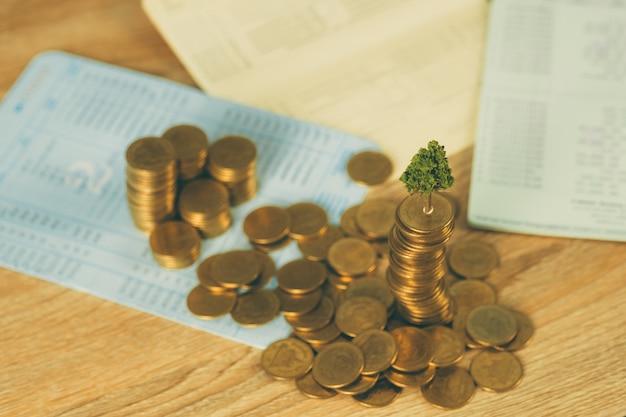 Árbol que crece en la pila de monedas de oro y libro de cuentas