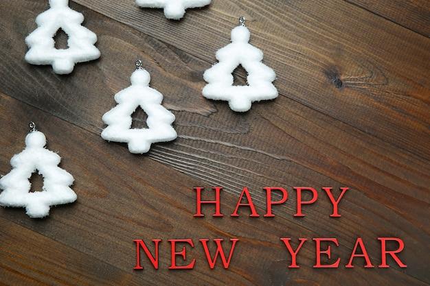 Árboles de navidad blancos y palabras de feliz año nuevo sobre fondo de madera