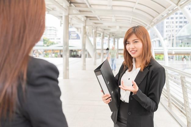 Archivo asiático holdind joven empresaria y mirando colega - concepto de negocio