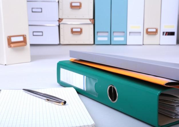 Archivo de carpeta, nota y bolígrafo sobre el escritorio.