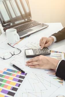 Archivos y carpetas y empresaria en segundo plano con calculadora