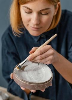 Arcilla de pintura de mujer de primer plano