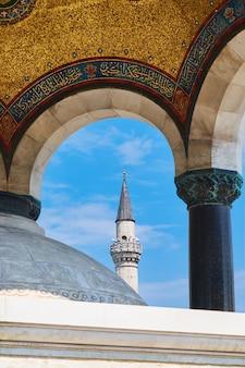 Arco bizantino con la parte superior de la torre del minarete entre columnas