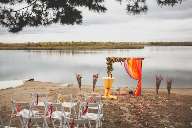 Arco de boda brillante delicado de flores y tela en la orilla arenosa de un río o lago. hermosa decoración de otoño, decoración de la boda. lugar de la boda en la playa
