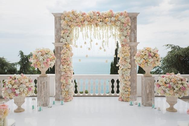 Arco de boda elegante con flores frescas, jarrones en el océano y cielo azul.