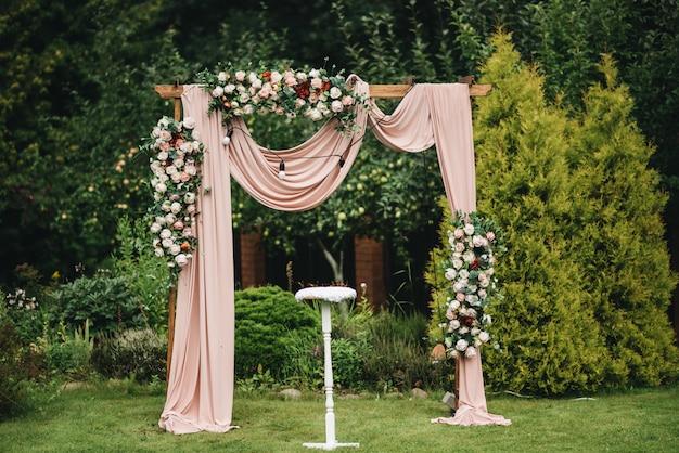 Arco para la ceremonia de la boda. arco, decorado con hermosas flores frescas y tela. inscripción en el lugar de matrimonio. arco de boda de flores reales. noche