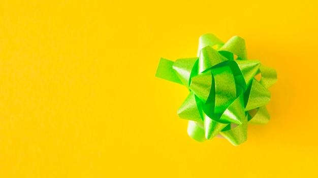Arco de cinta de raso verde sobre fondo amarillo