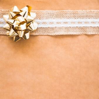 Arco de cinta dorada y rayas sobre papel marrón