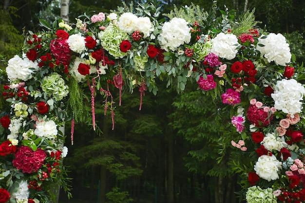 Arco floral de boda redondo de coloridas flores frescas al aire libre antes de la ceremonia de la boda