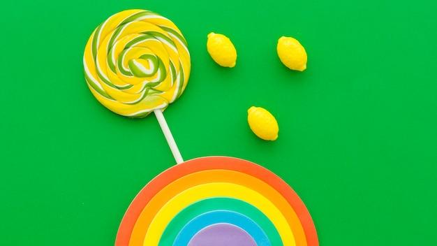 Arco iris cerca de caramelos de lollipop y limón sobre fondo verde