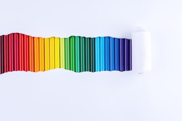 Un arco iris de lápices en una tira de papel blanco roto.