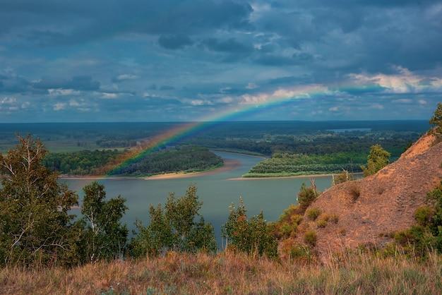 Arco iris con nubes sobre un valle fluvial
