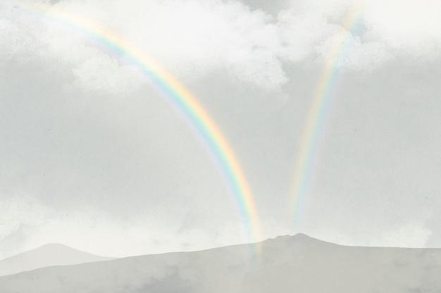 Arco iris sobre fondo de montañas con nubes