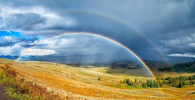 Arco iris sobre un hermoso campo verde y amarillo bajo el cielo nublado