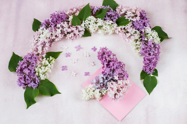 Arco de lilas y un ramo de lilas en un sobre.