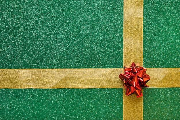 Arco rojo y cinta dorada adjunta a fondo verde