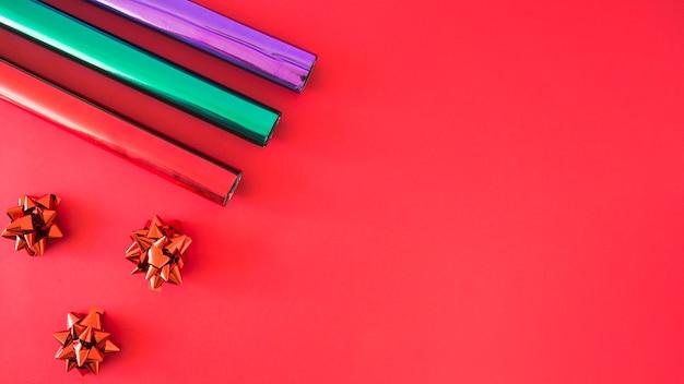Arco de satén rojo y tres rollos de papel de embalaje sobre fondo rojo