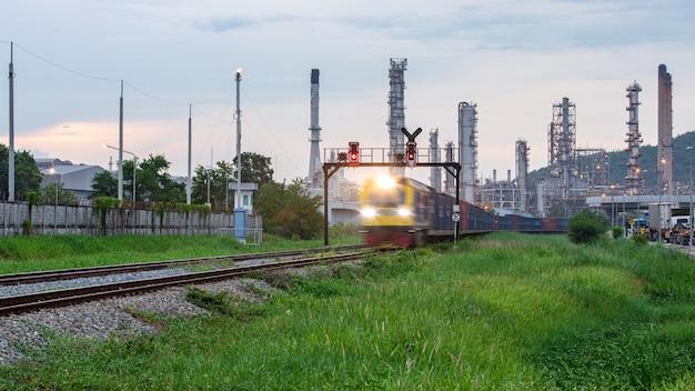 Área de almacenamiento de planta de refinería de petróleo y gas con tren en movimiento en primer plano y tarde en tailandia