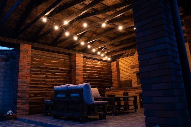 Área de barbacoa por la noche con bombillas antiguas. muebles de madera y palets.