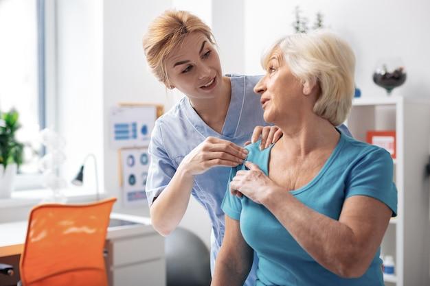 Área problemática. agradable mujer de edad apuntando a su hombro mientras muestra el área problemática a la enfermera