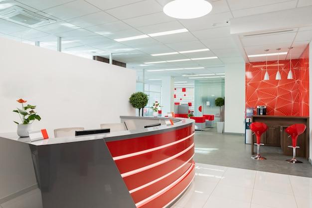 Área de recepción para visitantes de oficina moderna con interior rojo y blanco.