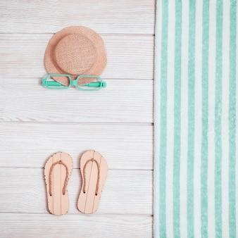 Área de salón de playa con zapatos de verano, gorro, toalla y gafas de sol.