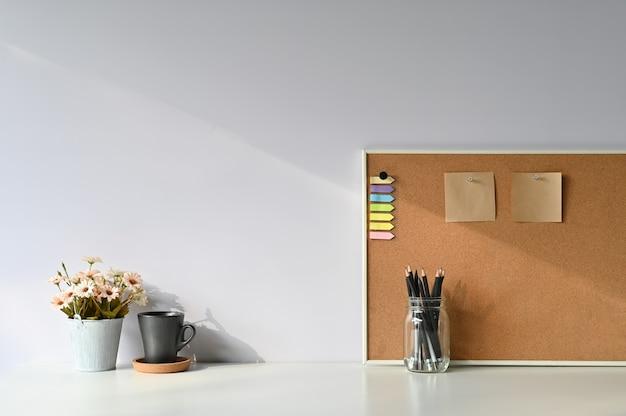 Área de trabajo café, lápiz, flor y una nota adhesiva a bordo con escritorio de oficina y luz de la mañana.