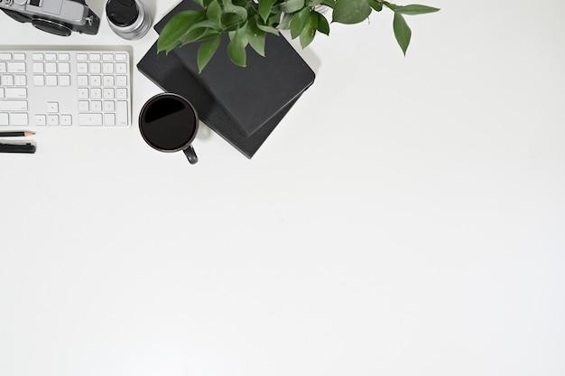 Área de trabajo vista superior teclado de computadora, café, cuaderno con decoración de plantas.