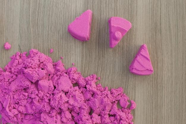 Arena cinética rosa brillante en manos de un niño