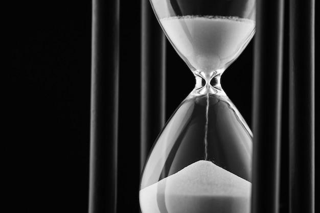 Arena corriendo por un reloj de arena de vidrio transparente