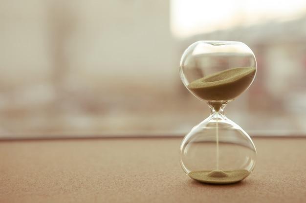 Arena corriendo a través de las bombillas de un reloj de arena que mide el tiempo que pasa en una cuenta regresiva para una fecha límite